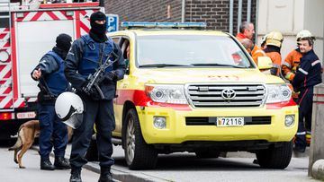 Armed police guard a street in the Brussels neighbourhood of Molenbeek, amid a manhunt for a suspect of the Paris attacks. (AAP)
