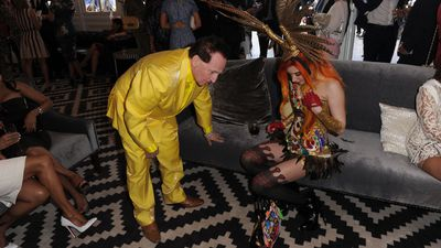 Gabi Grecko and Geoffrey Edelsten search on the floor for her engagement ring after dropping it in the Birdcage. (AAP)