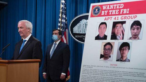An enlarged Wanted Poster is on display as Deputy Attorney General Jeffery Rosen speaks.