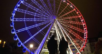Tourists look upon a ferris wheel lit up in the French national colours in Budapest, Hungary. (AAP)