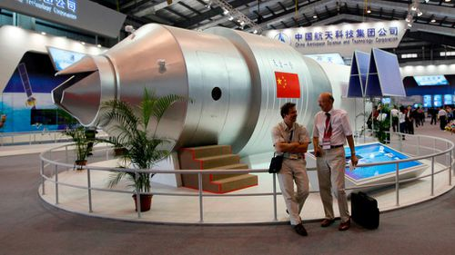 Visitors sit beside a model of China's Tiangong-1 space station at the 8th China International Aviation and Aerospace Exhibition in Zhuhai in 2010. (AP)