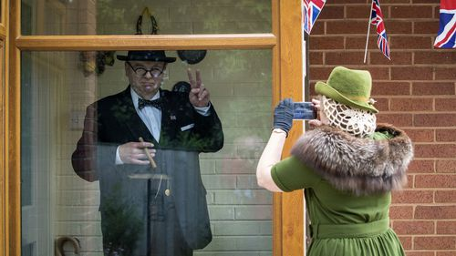 Derek Herbert a Sir Winston Churchill impersonator from Little Neston, Wirral, England is dressed up to mark the 75th anniversary of VE Day with his wife Linda who is dressed as Clementine Churchill Friday May 8, 2020.