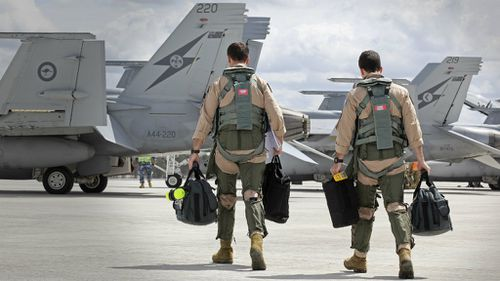 F/A-18F Super Hornet aircrew head to their aircraft in preparation for departure to the Middle East. (ADF)