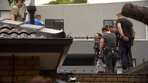 Police coaxed the suspect down from the roof, then arrested him.