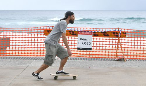 A man on a skateboard is seen going past the closed off Surfers Paradise beach on the Gold Coast, in April.