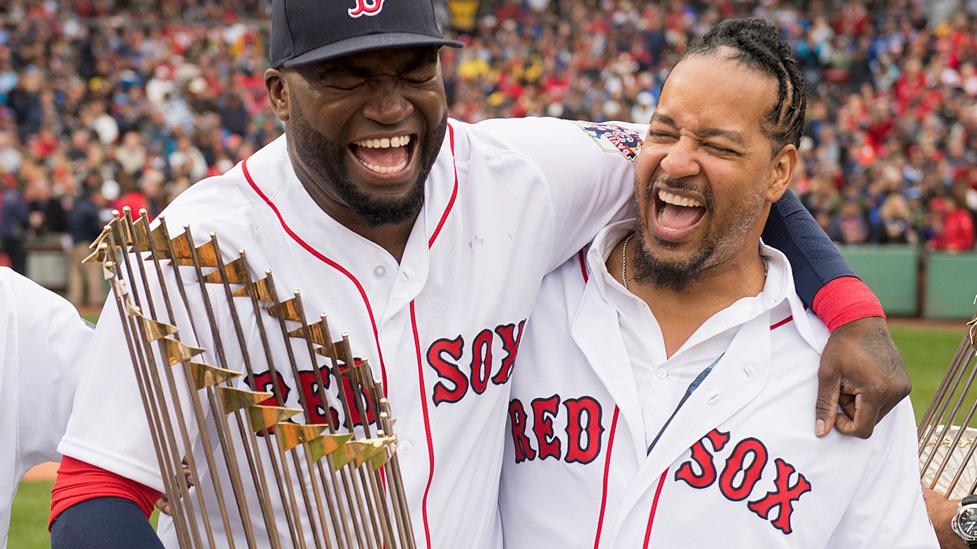 David Oritz #34 of the Boston Red Sox laughs with former teammate Manny Ramirez