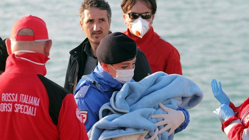 A Red Cross worker carries a baby rescued from the stricken ship. (AAP)