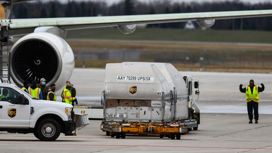 Some of the first shipments of the Pfizer COVID-19 vaccines are seen Sunday, Dec. 13, 2020, on the tarmac at Capital Region International Airport in Lansing, Michigan. (AP Photo/Matthew Dae Smith via Lansing State Journal)
