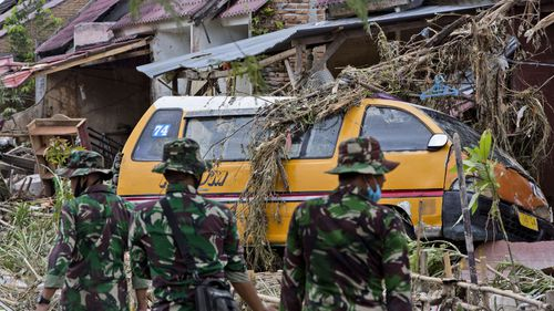 Indonesian soldiers examine the damage at a neighbourhood affected by a flood in Medan, North Sumatra, Indonesia, Friday, Dec. 4, 2020