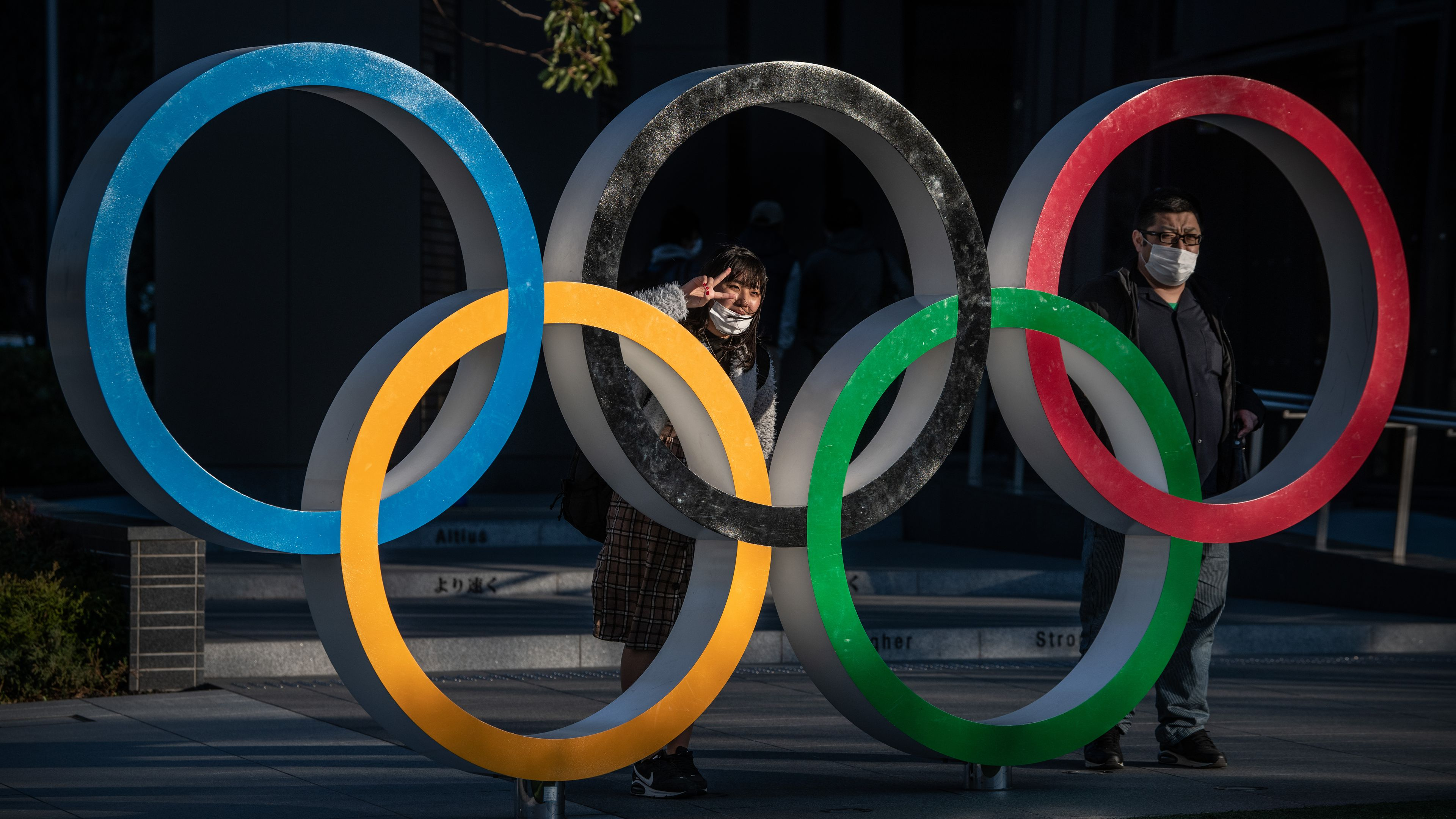 People wearing face masks pose for photographs next to Olympic Rings.