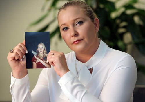 Virginia Roberts Giuffre holds a photo of herself at age 16, when she says now dead Palm Beach multi-millionaire Jeffrey Epstein began abusing her sexually.