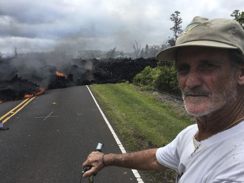 Resident Sam Knox, 65, rides his bicycle to the edge of the road as lava burns across the road. (AAP)