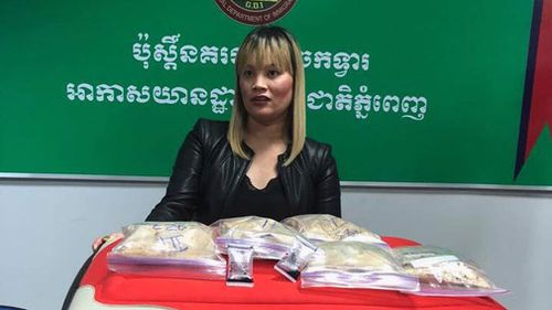 Ve Thi Tran pictured with her suitcase and the heroin allegedly found inside it. (Image: Cambodia General Department of Immigration/Facebook)