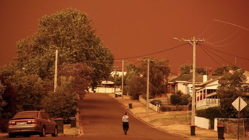 A woman looks down her street as the sky turns red from the fires on January 04, 2020 in Bruthen Australia. Evacuations Continue Across East Gippsland As State Of Disaster Is Declared