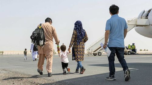 A family on the tarmac at Kabul Airport prepares to board a flight taking them to Australia.