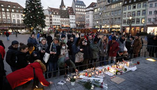 People light candles and leave signs and flowers on a place close to the Christmas Market where a shooting happened in Strasbourg, France