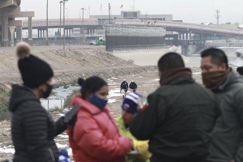 Sebuah keluarga migran Kuba ditahan oleh tentara Garda Nasional di sepanjang Rio Grande di Ciudad Juarez, Meksiko, pada 16 Februari 2021.
