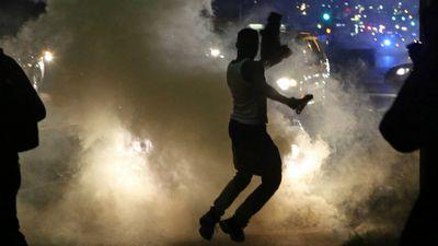 Protesters run when the police shoot tear gas in Ferguson. (AAP)