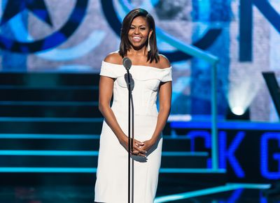 <p>The First Lady chose a white off-the-shoulderZac Posendress and metallic silverJimmy Choopumps at BET's 2015 Black Girls Rock event.</p> <p>Image: Getty.</p>