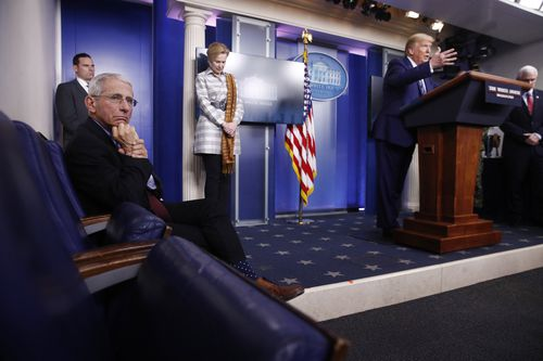Dr Anthony Fauci, director of the National Institute of Allergy and Infectious Diseases, listens as President Donald Trump speaks during a coronavirus task force briefing at the White House