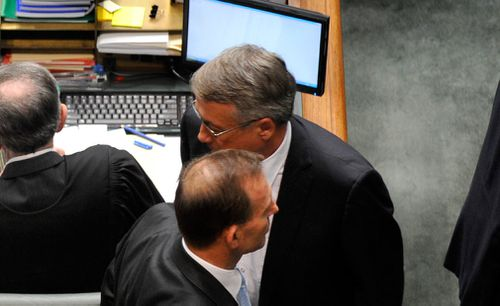 Mr Abbott and Mr Swan cross paths during a division in question time in the House of Representatives in May 2012. (Image: AAP)