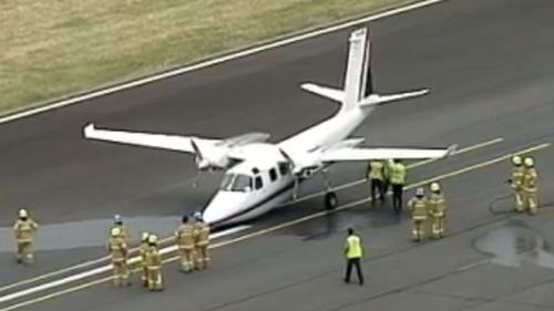 Emergency crews surround the plane after it touches down. (9NEWS)