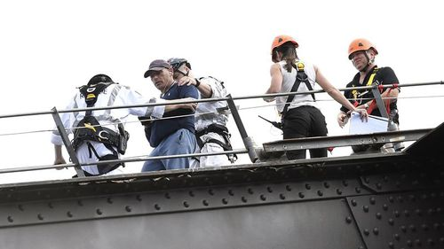 Mr Cook was arrested and escorted off the bridge by police just before 10am. (AAP)