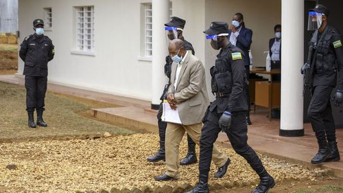 "Paul Rusesabagina, center, whose story inspired the film ""Hotel Rwanda"", is led out in handcuffs from the Kicukiro Primary Court in the capital Kigali, Rwanda Monday, Sept. 14, 2020"