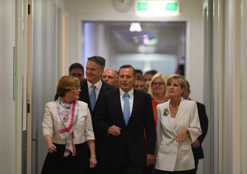 Prime Minister Tony Abbott and fellow MPs arrive for a special Liberal party room meeting at Parliament House in Canberra.