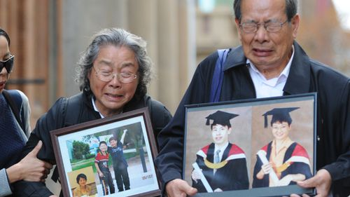 Granfather Yang Fei Lin  and grandmother Feng Qing Zhu leave court carrying photographs of their murdered family members. (AAP)