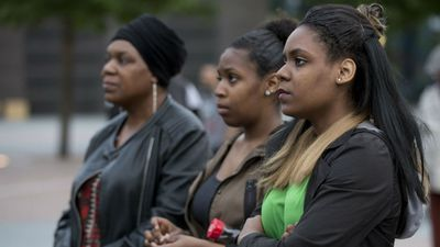 Spectators watch live streams of the memorial around the world – here, women watch from south London. (AP/Isabel Infantes)