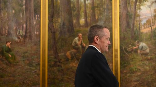 Bill Shorten walks past the painting 'The Pioneer' by Frederick McCubbin.