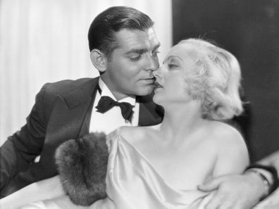 Studio portrait of Clark Gable and Carole Lombard kissing.