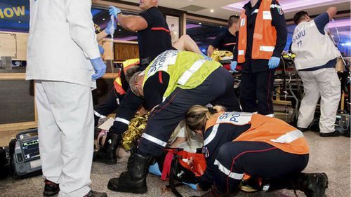 Rescue workers tending to a victim after a man deliberately rammed his car into a pizzeria in Sept-Sorts, east of Paris. (AAP)