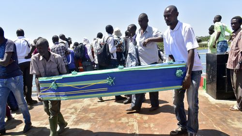 Relatives carry coffins to be used for the victims of the MV Nyerere passenger ferry on Ukara Island, Tanzania. (AAP)