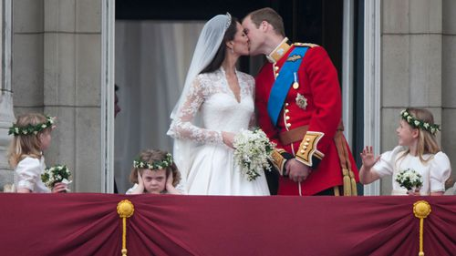Duchess and Prince William sharing the famed balcony kiss on their wedding day.