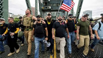 Members of the Proud Boys and other right-wing demonstrators march across the Hawthorne Bridge during a rally in Portland, Oregon.