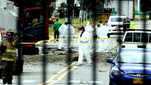 Forensics experts pick their way through the bomb site