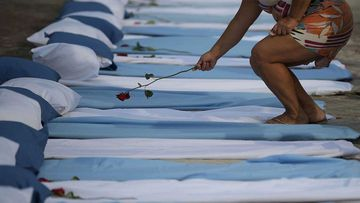 A woman is shown laying a rose on top of a mattress symbolising COVID-19 victims during a protest outside a hospital in Rio de Janeiro, Brazil.