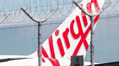Virgin Australia jet behind razor wire (Getty)