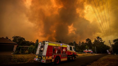 Firemen prepare as a bushfire approaches homes on the outskirts of the town of Bargo on December 21, 2019 in Sydney, Australia.