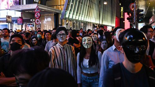 People in Guy Fawkes masks gather on the street during Halloween celebration.