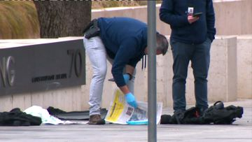 An armed, plain clothes officer looks over items on the ground, in front of the ASIO headquarters.