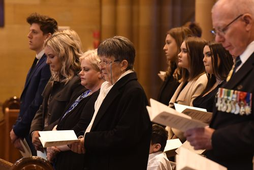 Pauline Johnson (centre) sits with her grandchildren during the State Funeral for her husband John Richard Johnson at St Mary's Cathedral. (AAP)