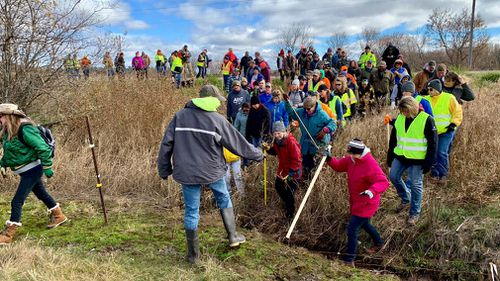 Volunteers cross a creek and barbed wire near Barron, Wisconsin, on their way to a ground search for 13-year-old Jayme Closs.