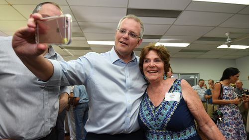 Prime Minister Scott Morrison takes a selfie with a supporter during a CWA hall meeting in Maroochydore on the Sunshine Coast.