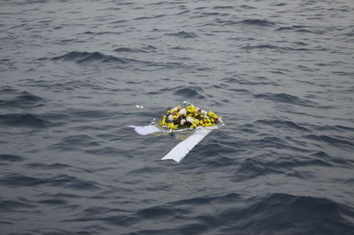 A wreath lays in the water at the scene of the crash site.