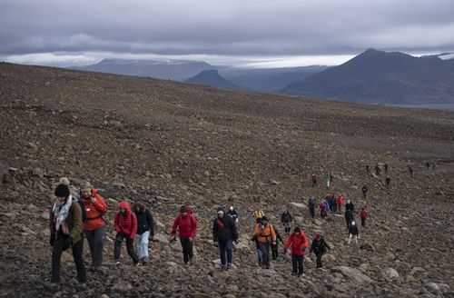 People climb to the top of what once was the Okjokull glacier, in Iceland