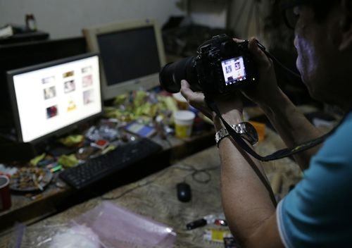 A Filipino member of the National Bureau of Investigation takes a picture of the computer of suspected child webcam cybersex operator, David Timothy Deakin, during a raid at his home in Mabalacat, Philippines.  (AAP)