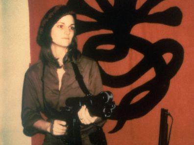 Kidnapped heiress Patty Hearst holding a machine gun.
